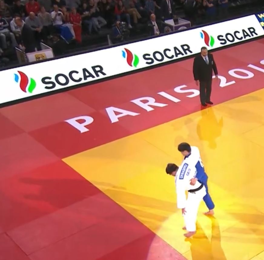 Judoka helping injured opponent after winning a fight at an international tournament