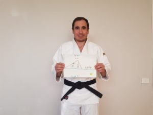 Sensei Clau holding the custom made book made by Juki Dojo's students
